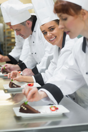 Team of chefs in a row garnishing dessert plates one girl smiling at camera in busy kitchen photo