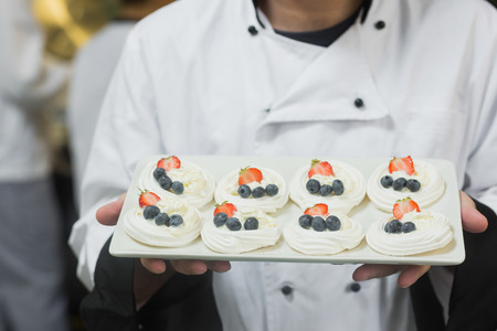 Chef presenting plate of meringues in commercial kitchen photo