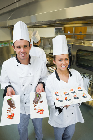 Two young chefs presenting dessert plates smiling at the camera  photo