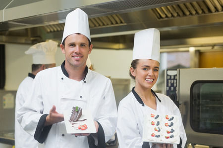Two proud chefs presenting dessert plates in the kitchen smiling at the camera photo