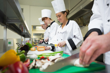 chopping: Four chefs preparing food at counter in a row in a professional kitchen Stock Photo