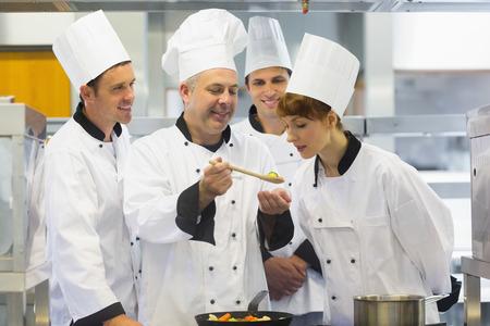 les geven: Hogere chef-kok tonen van voedsel aan zijn collega's terwijl ze in de keuken