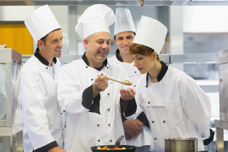 chefs whites: Senior chef showing food to his colleagues while being in the kitchen