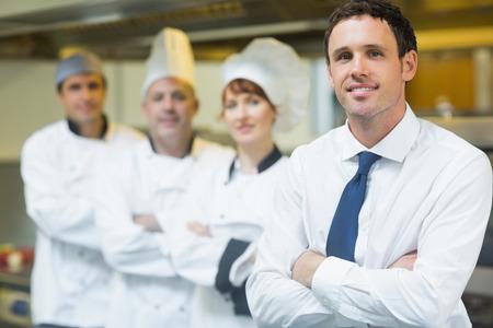 Jonge restaurant manager poseren voor team in restaurant