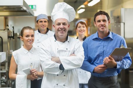 プロフェッショナルなキッチンで彼の背後にあるチームとポーズのヘッドシェフ