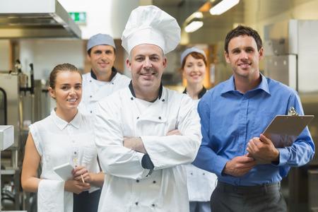 Chef-kok poseren met het team achter hem in een professionele keuken Stockfoto