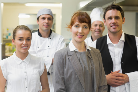 Young female manager posing in a modern kitchen with the staff photo