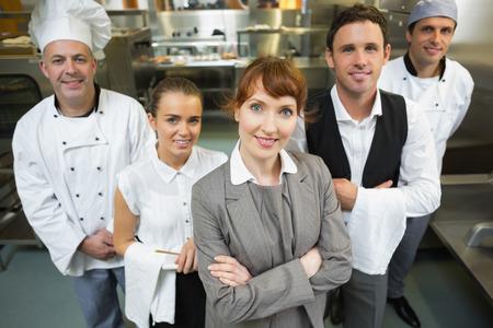 mesero: gerente mujer linda que presenta con el personal en una cocina moderna