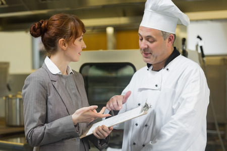 organising: Young female manager talking to the head cook standing in a professional kitchen