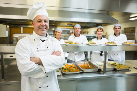 Proud mature head chef posing in a modern kitchen with his colleagues in the background photo