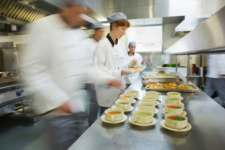 busy restaurant: Four chefs working in a modern kitchen preparing soups