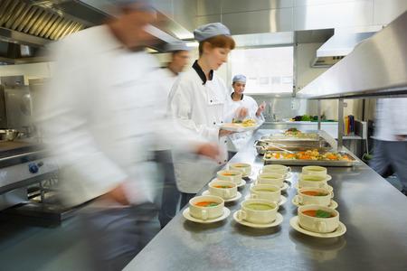 Vier koks werken in een moderne keuken bereiden soepen