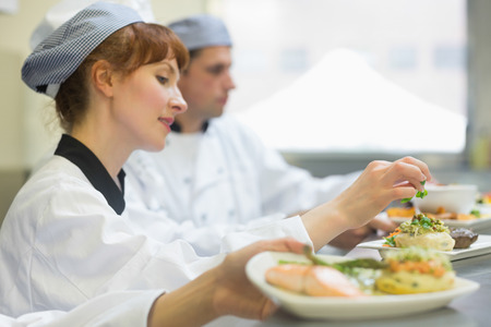 female chef: Young female chef preparing a plate in a professional kitchen Stock Photo