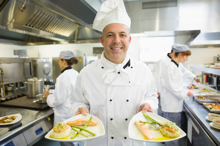 Mature head chef presenting proudly some dinner plates in a busy kitchen photo