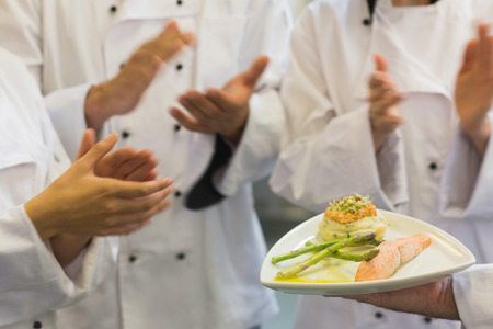 Chefs applauding a salmon dish in commercial kitchen photo