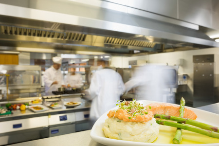 kitchen restaurant: A plate with salmon asparagus and mashed potato in a busy kitchen Stock Photo