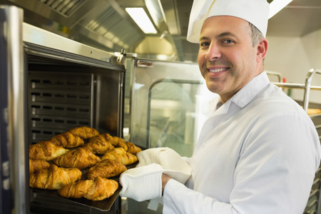 Mature baker smiling proudly at the camera take some croissants out of oven Stock Photo