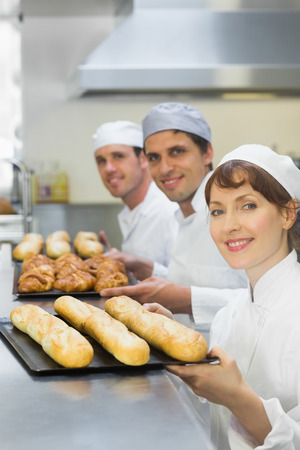 Three young bakers holding baking trays with food on them
