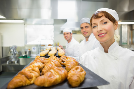 Three young bakers standing in a bakery  smiling at the camera  photo