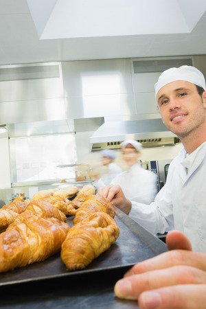 Young male baker standing in a bakery in front of a baking tray with croissants photo