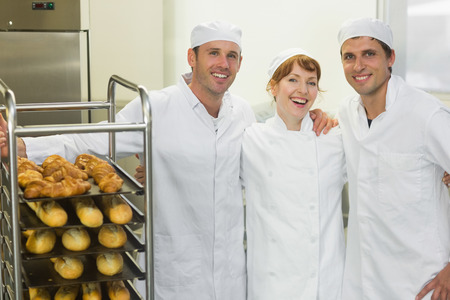 Three young bakers posing together in a bakery wearing work coats photo