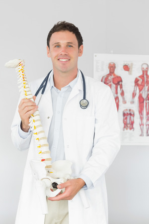 Handsome cheerful doctor holding skeleton model in bright office photo