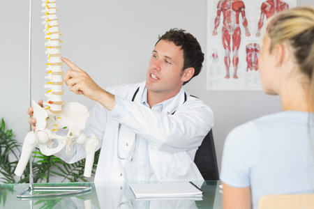Handsome doctor showing a patient something on skeleton model in bright office photo