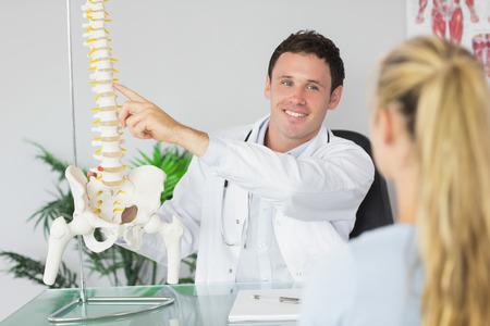 skelett mensch: L�chelnder Doktor, der ein Patient etwas auf Skelettmodell in hellen B�ro