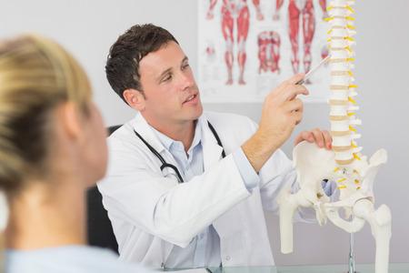 skelett mensch: Gut aussehende Arzt mit einem Patienten etwas auf Skelettmodell in hellen B�ro