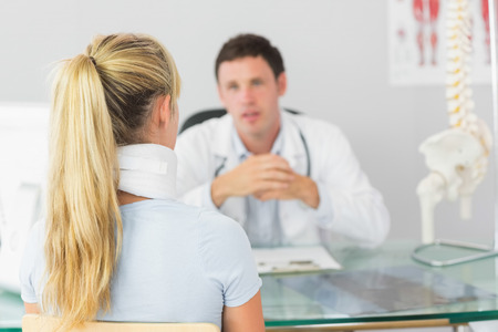 Attractive doctor having an appointment with a patient in bright office photo