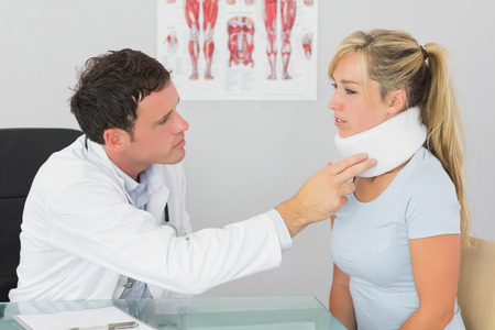 Attractive doctor examining neck of a patient in bright office photo