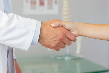 Close up of patient shaking hands with doctor in bright office photo