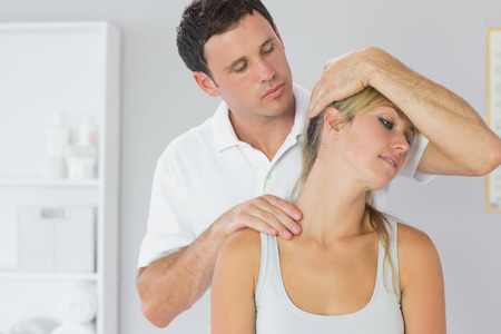 Attractive physiotherapist examining patients neck in bright office photo