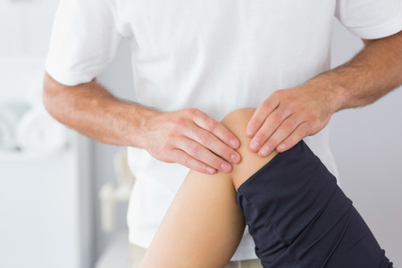 Physiotherapist checking knee of a patient in bright office photo