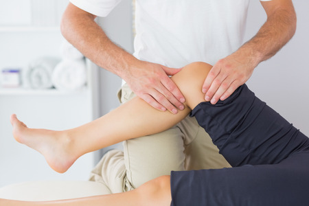Physiotherapist controlling knee of a patient in bright office photo