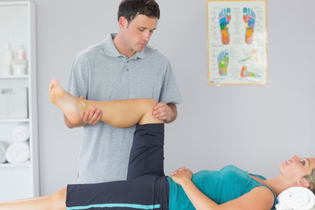 Good looking physiotherapist controlling knee of a patient in bright office photo