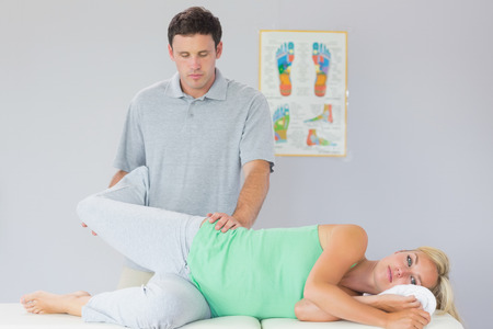 manipulating: Handsome physiotherapist manipulating patients leg in bright office