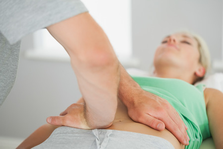 alignment: Physiotherapist checking patients pelvis alignment in bright office