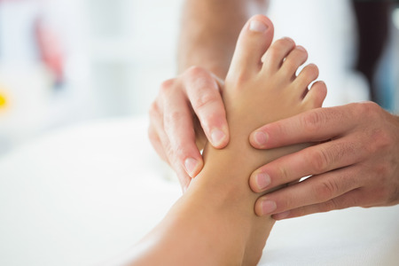 Close up of physiotherapist massaging patients foot in bright office Фото со стока
