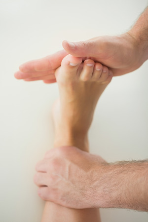 Close up of physiotherapist treating patients foot in bright office photo