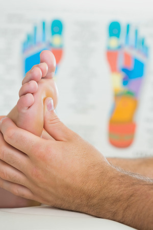 Close up picture of physiotherapist massaging a patients foot in bright office photo