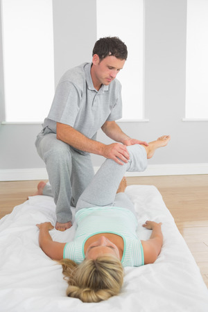 Physiotherapist examining patients leg on a mat on the floor in bright room photo