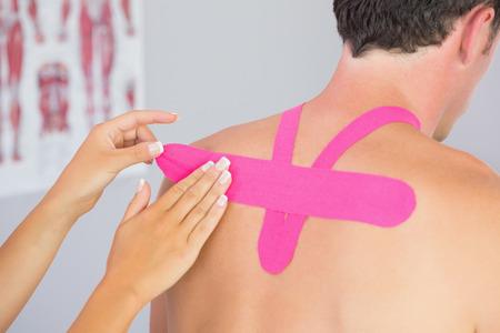 Physiotherapeut setzen auf rosa Kinesio Tape m�nnlichen Patienten zur�ck in hellen B�ro
