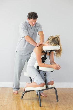 massage chair: Masseur treating clients back in massage chair in bright room Stock Photo