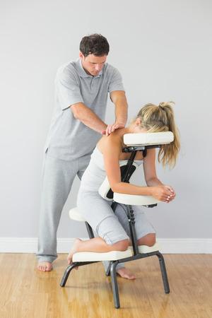 Masajista que tratar a los clientes de vuelta en la silla de masaje en la habitación luminosa