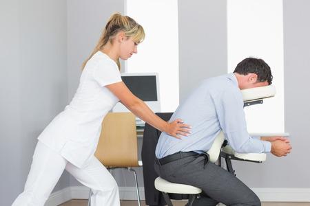 massage homme: Masseuse traiter les clients bas du dos dans chaise de massage dans la salle lumineuse