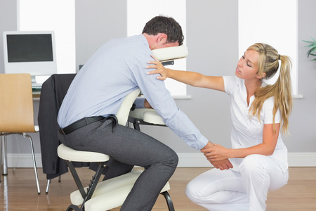 arm chair: Masseuse treating clients arm in massage chair in bright room