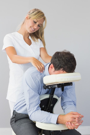 Masseuse treating clients neck in massage chair in bright room Stock Photo