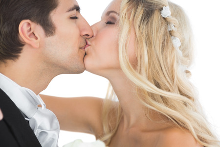 Attractive married couple kissing each other on white background photo