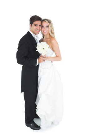 blonde couple: Cute young married couple posing holding a white bouquet smiling at camera